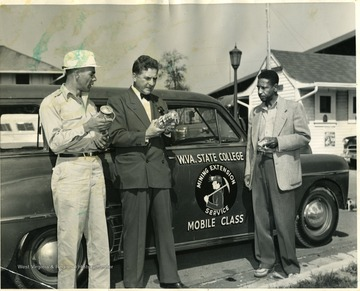 Three men inspecting lanterns next to a W. Va. State College Mining Extension Service Mobile Class car.