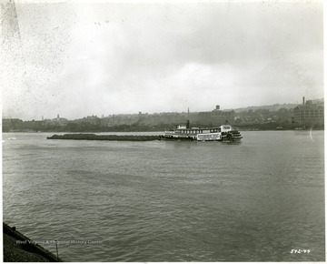 Pittsburgh Coal Co. towboat with a load of coal outside of an unknown city.