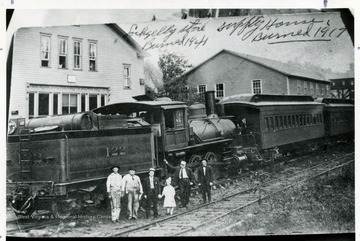 Group of men and child pose in front of train No. 122 at Lochgelly station. Left is the Lochgelly store which burned in  1941. Right is the Supply House which burned in 1917.