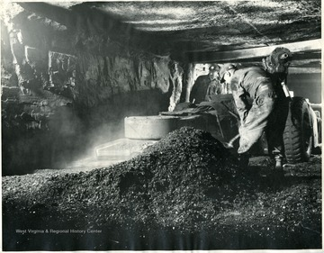 Two miners digging coal in mine.