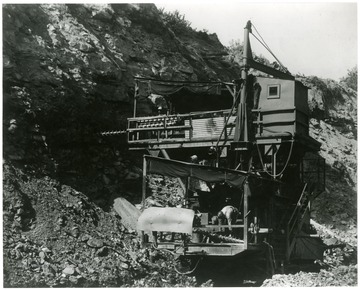 Caption on back reads, 'Stiff-arming a highwall is the job of this new, double-decker drill in operation at the Georgetown mine, Hanna Coal Co., at Georgetown, Ohio. Fruit of the ingenuity of coal mining engineers, the drill makes two blast holes at different levels in the highwall, permitting a blasting shot that brings down a large section of 'overburden.' The 'overburden,' rock, shale, limestone, clay and other mineral deposits, lies above the coal seam. Surface, or open-pit mining, accounts for 23 percent of total bituminous production. The Georgetown mine is the largest surface mine in the world.'