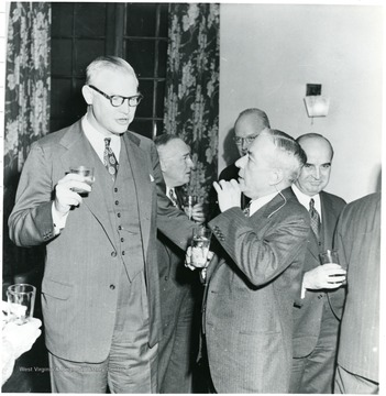 Two coal officials with drinks talking.