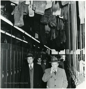 Men walking through locker room during a Consolidation Coal Co. Inspection trip.