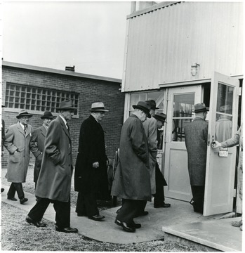 Coal officials entering building during a Consolidation Coal Co. Inspection trip.