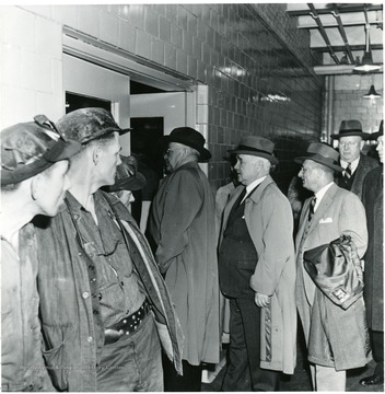 Three miners watch a line of coal officials entering a room during a Consolidation Coal Co. Inspection trip.