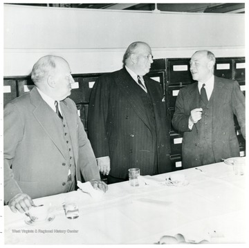 Three coal officials talking behind a table during a Consolidation Coal Co. Inspection trip.