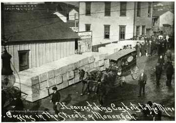 Caskets lining the street as horse-drawn hearse takes caskets to the mine.
