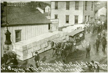 Street scene after Monongah disaster. Horse-drawn hearse delivers caskets to the mine and coffins line the street of Monongah.