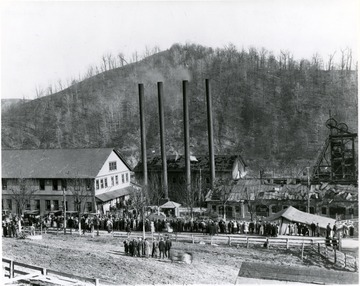 Crowds gather outside mine buildings after an explosion.
