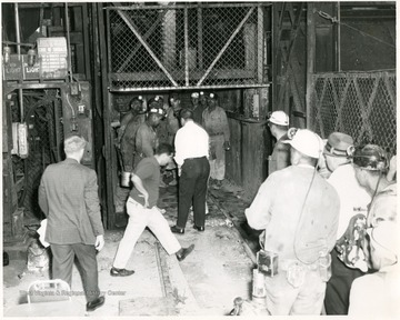 Men leaving an elevator after a mine accident in Monongalia County.