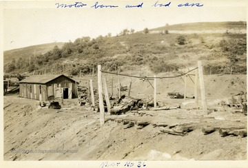 Mine No. 36 motor barn with broken mine cars outside of it.