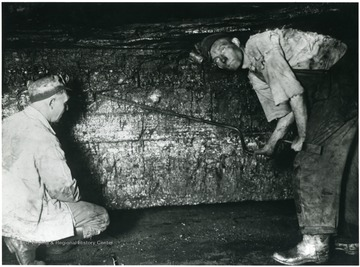 "'White Oak preparation begins when the machine leaves and the miner is ready to shoot down his coal. The shooting inspector on the left has not only located the hole for the miner to drill, but instructed him as to what angle he must bore his hole to contain the necessary explosive used in dislodging the coal from the seam. The ""kerf"" made by cutting machine is plainly visible in this picture and you will note the cutting or ""bug dust"" have been removed before the coal is shot. The length of the auger used by the miner and the width of the bit which determines the size of the hole bored, is also carefully regulated.'"