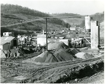 Miners working with machinery near coal preparation plant. There is a church visible in the background.