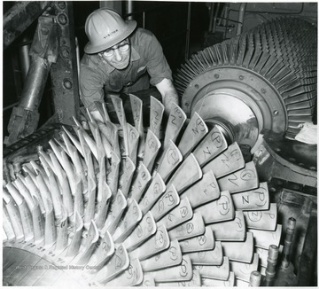 Mechanic working on what appears to be a turbine.