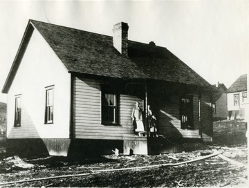 Women and child stand on porch of cottage.