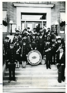 Group portrait of the New River Coal Company band in uniform standing on steps.