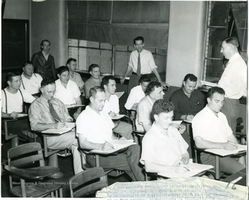 Group of mine foremen listen during an instruction course.  Center rear is Clyde Sutherland.
