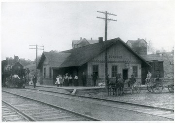 Group of people wait at the train station as a train comes in.