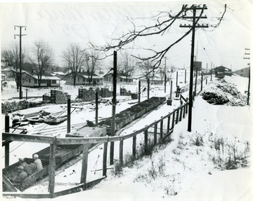 Men riding in coal cars along snow covered tracks to the Skelton mine during winter time.  Miner's homes and wood piles visible.