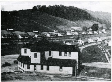 Section of town of Whipple, West of the company store showing store in the foreground, miner's homes in the distance.