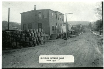 Side view of the bottling plant at MacDonald.  Barrels stacked beside the plant building.