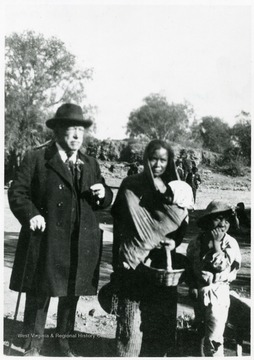 Portrait of Samuel Gompers in Mexico standing with a mother with children.