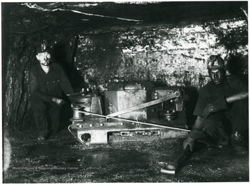 'All White Oak mines are electrically equipped and of course this mining machine is operated by electricity. The machine is mounted and transported on a specially designed truck and moves under its own power from one working place to another. It is taken from the truck by the machine operator and his helper and moved to the place of the coal and place in cutting position as you see it in this picture. The machine consists of an endless chain with 'bits' inserted, which act as cutters. The machine cuts a 'kerf' or hole along the bottom of the coal about 4 inches high and extending back six feet under the coal. The fine coal made by this machine is what is commonly known as 'bug dust.' Cutting machines are operated at night and each machine is capable of cutting twenty places on each shift. These machines are operated on tonnage basis and these operators earn high wages.'