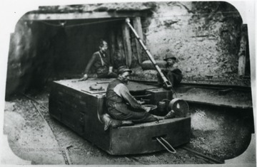 Miners on an electric locomotive used in hauling mine cars.