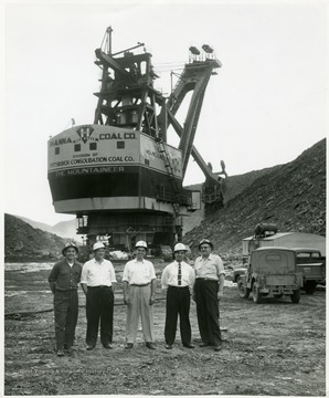 Group portrait of visitors in hard hats in front of the giant shovel the Mountaineer.