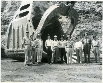 Group of men stand in front of a giant shovel scoop in Cleveland, OH.
