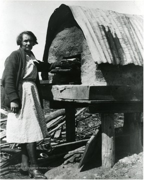 Picture of Mrs. Marin preparing a meal in her outdoor oven.