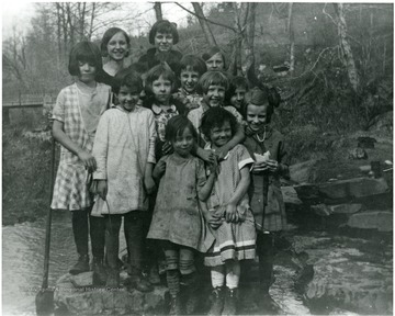 Picture presents unidentified girls near a creek.
