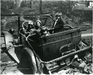 Picture presents unidentified girls playing in a wrecked car.