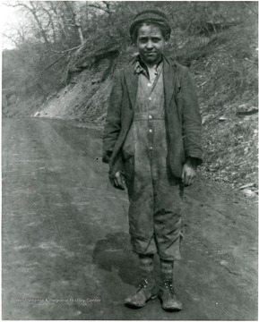 Eugene Collings standing on a dirt road.