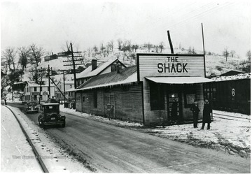Two unidentified men standing in front of the Shack building on a winter day.