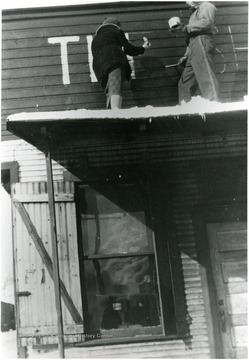 Mary Behner(later Christopher)and George Lay painting the name on the building's facade.