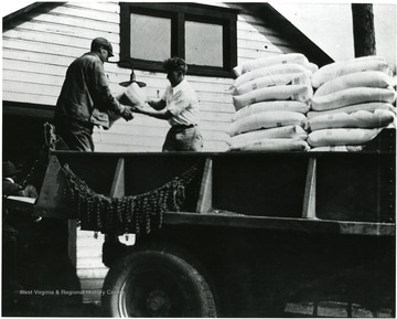 Two men unloading a truck delivery to the Shack.