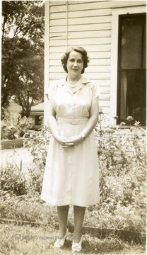 Portrait of Katherine Estenline, Director of Scott's Run Methodist Settlement House 1939-1941 standing outside a building near a flower garden.