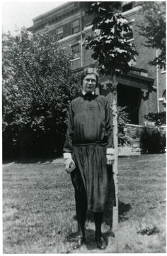 Portrait of Frances Kruger, Director of Scott's Run Settlement House 1929-1933 standing beside tree and in front of large brick building.