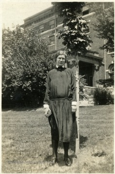 Portrait of Frances Krurger, Director of Scott's Run Settlement House 1929-1933 standing beside tree in front of large brick building.