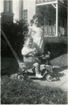 Helen Digit (standing) and John Digit III at 2 years old(sitting on a riding toy), Children of Luella Digit, Director of the Settlement House, 1936-1938.