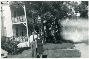 Luella Digit (worker at Scott's Run) and husband standing in yard of house 1936-1938.