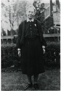 Julia A. Lakey, Director of Scott's Run 1924-1925 standing in front of hedges and wooden fence.
