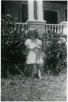 Helen Digit (age five), Luella Digit's daughter, standing in front of building with the number 504 above the door.