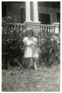 Helen Digit (Age Five), Luella Digit's daughter standing in front of a building with the number 504 above the door.