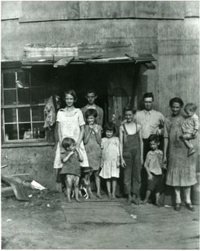 Unidentified family with their pet in front of a house in Scott's Run, W. Va.