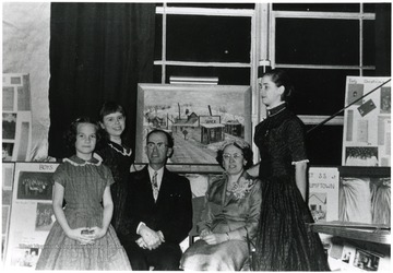 Group portrait of the Mary Behner Christopher family in front of a painting of the Shack.