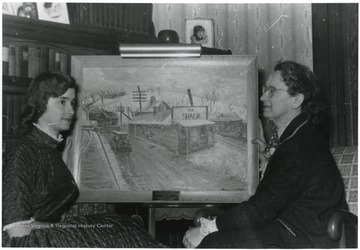 Artist Margaret Anne Christopher(left) and her Mother Mary sit in front of a painting of the Shack.