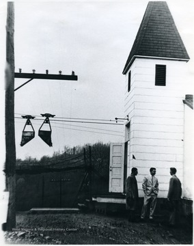 Three men stand outside Canyon Chapel church building. One of the Mountaineer Mining Mission Chapels, Monongalia County, W. Va. 'For information on the Mountaineer Mining Mission See A&M 2491 (SC).'