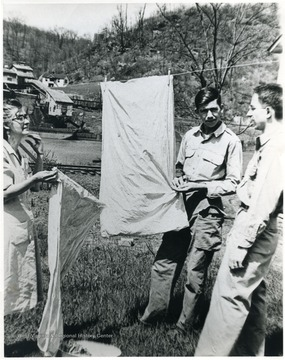 Two men and a lady hanging clothes to dry in Marion County, W. Va. 'For information on the Mountaineer Mining Mission, See A&M 2491 (S.C.).'
